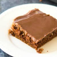 Classic Chocolate Sheet Cake Recipe - This delicious sheet cake (some call it a Texas Sheet cake or a sheath cake) is rich and dense, almost like a brownie. Grab the recipe and learn more about this classic American dessert recipe!