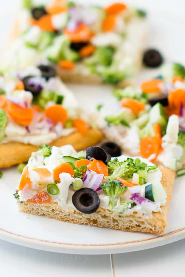 Cold Vegetable Pizza - This cold veggie pizza recipe is made with crescent rolls, cream cheese, ranch dressing and lots of fresh veggies. It's the perfect party appetizer or fun family meal!