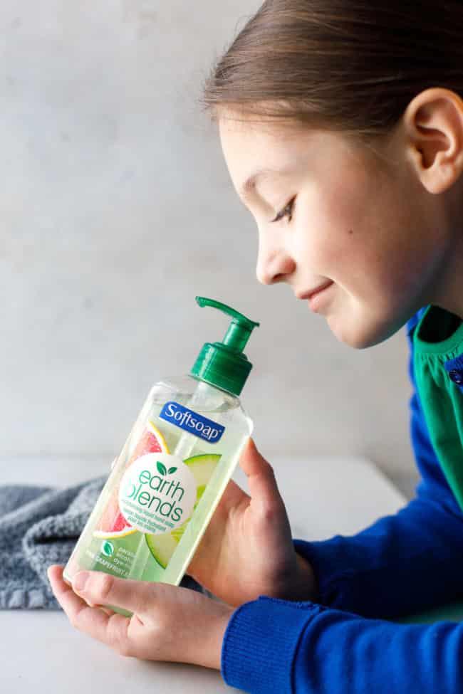 girl holding a bottle of soft soap earth blends