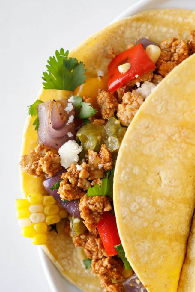 Ground Pork tacos on corn tortilla with roasted veggies, cilantro and cotija cheese