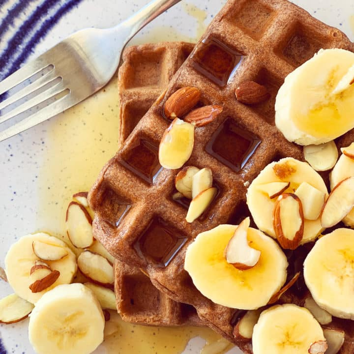 chocolate waffle with syrup and banana on plate